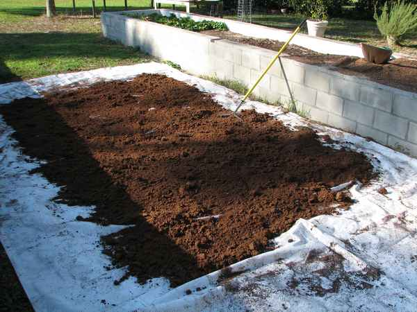 We always start with the Peat Moss. It comes in a compressed bale, so it has to be broken apart until it is all the same consistency. The flat side of a rake is used to spread it out, then just stepping on the chunks breaks it down.