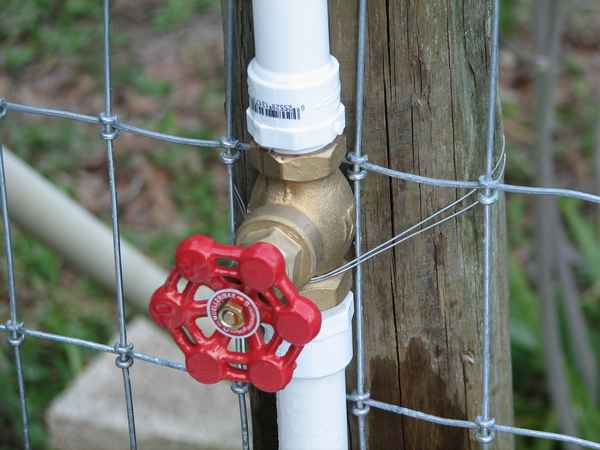 Stainless steel wire is used to secure the valve to the fence post.